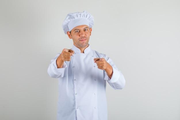 Mężczyzna kucharz w kapeluszu i mundurze, wskazując palcami wskazującymi na aparat i patrząc pewnie