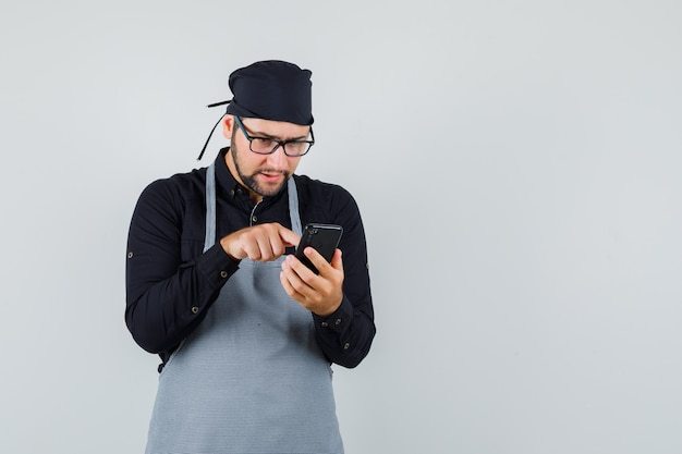 Mężczyzna kucharz w koszuli, fartuch wpisując na telefon komórkowy i patrząc zajęty, widok z przodu.