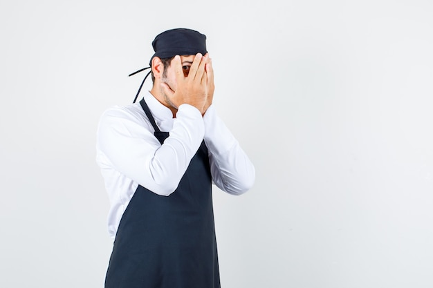 Mężczyzna kucharz w mundurze, fartuch patrząc przez palce jednym okiem i wyglądający nieśmiało, widok z przodu.