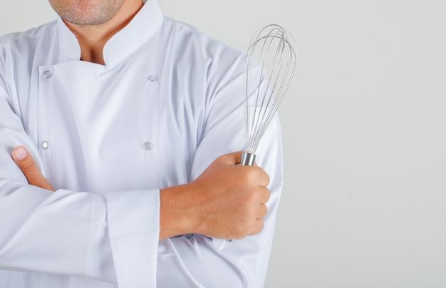 Mężczyzna kucharz w mundurze trzymając trzepaczkę ze skrzyżowanymi rękami