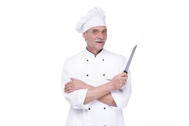 Mężczyzna kucharz w mundurze trzymający metalowy nóż, pozostając na białej ścianie