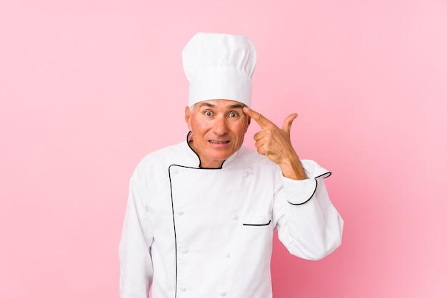 Mężczyzna kucharz w średnim wieku na białym tle pokazując gest rozczarowania z palcem wskazującym.