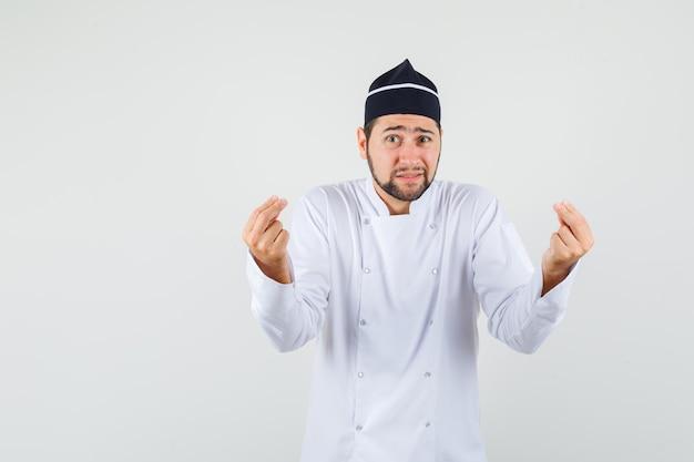 Mężczyzna kucharz wyjaśniający coś w białym mundurze i wyglądający na bezradnego, widok z przodu.