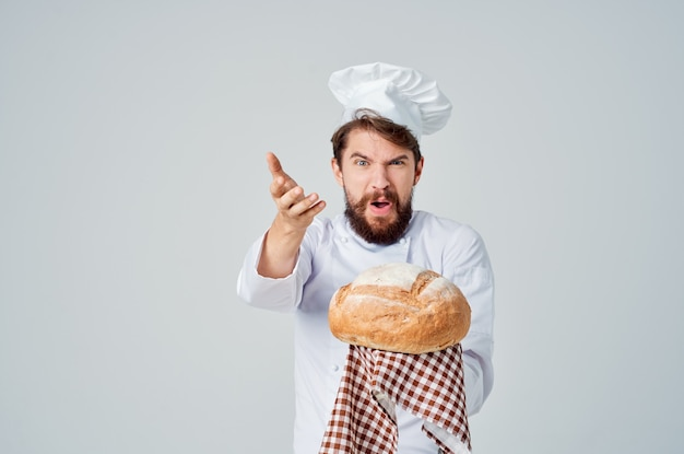 Mężczyzna kucharz z chlebem w dłoni jasnym tle