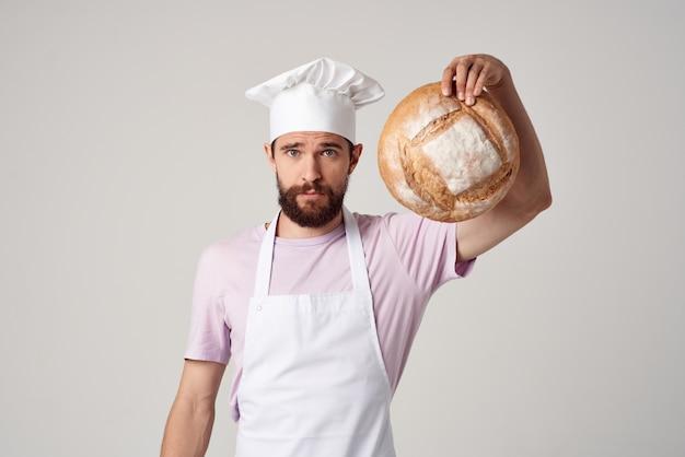 Mężczyzna kucharz z chlebem w rękach gotuje do pieczenia
