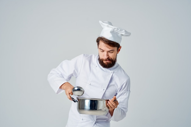 Mężczyzna kucharz z rondelkiem w rękach praca profesjonalna kuchnia styl życia