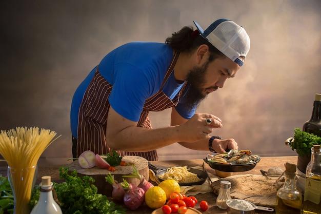 Mężczyzna kucharza szefa kuchni modniś z przystojną brodatą twarzą w kapeluszu