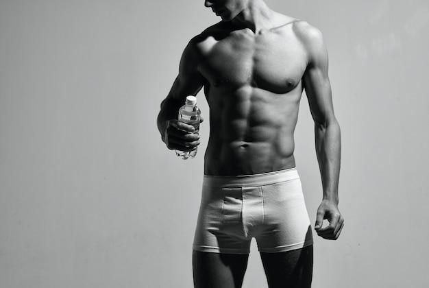 Mężczyzna kulturysta w białych spodenkach pozowanie treningu sportowca