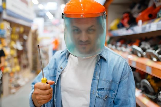 Mężczyzna kupujący w masce trzyma śrubokręt, sklep z narzędziami. klient patrzy na towary w sklepie dla majsterkowiczów, robi zakupy w supermarkecie budowlanym