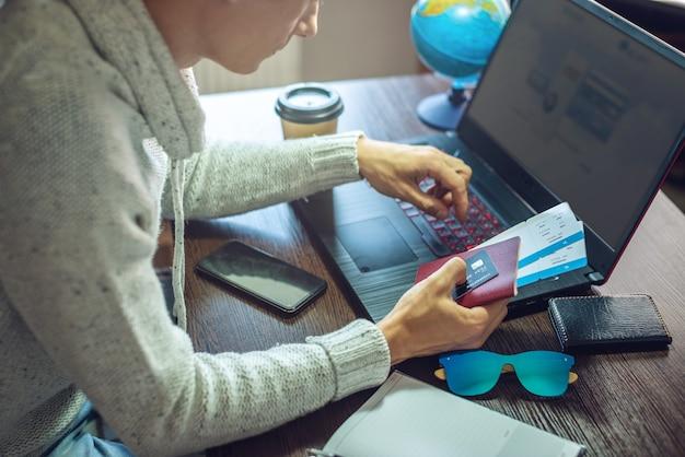 Mężczyzna kupuje bilety lotnicze przez internet, korzystając z laptopa w długo oczekiwaną podróż
