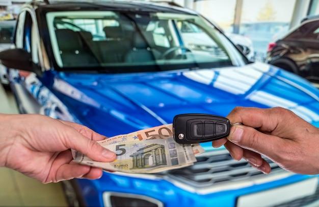 Mężczyzna kupuje nowy samochód, dając banknoty euro. koncepcja zakupu finansów