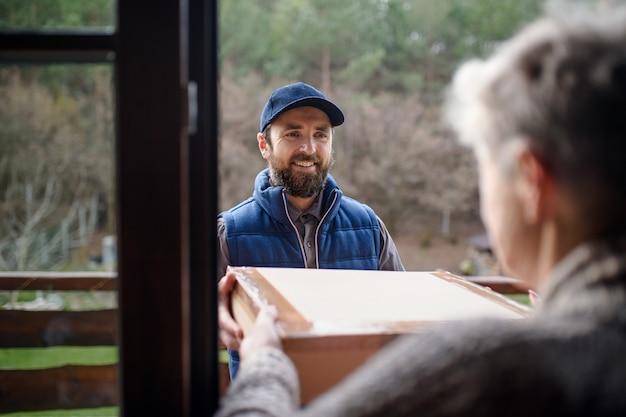 Mężczyzna kurier dostarczający paczkę do starszej kobiety, stojącej przy drzwiach.
