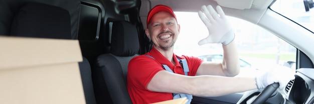 Mężczyzna kurier kierowca w kabinie samochodu macha ręką na powitanie
