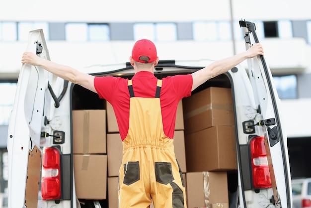 Mężczyzna kurier otwierający samochód minivan z wieloma kartonami