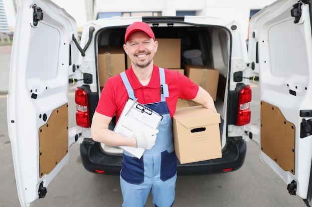 Mężczyzna kurier trzymający dokumenty dostawy i karton w pobliżu samochodu