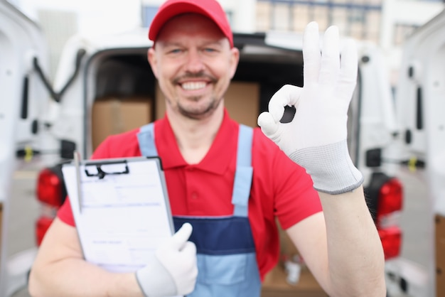 Mężczyzna kurier trzymający dokumenty i pokazujący dobry gest w pobliżu samochodu z pudełkami