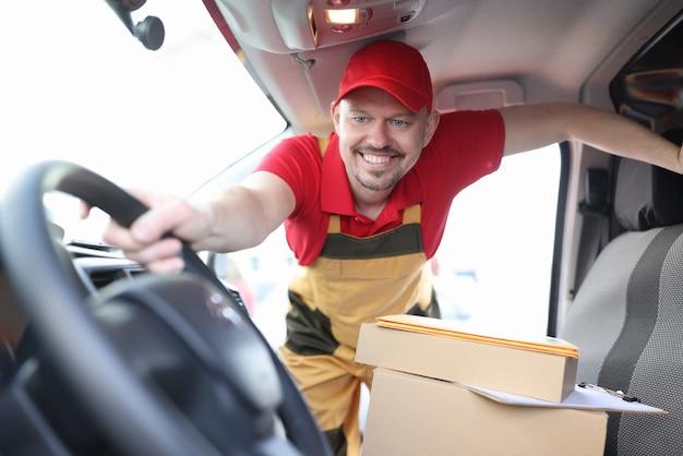 Mężczyzna kurier trzymający koło samochodu z pudełkami