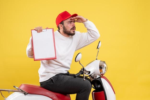 Mężczyzna kurier trzymający notatkę z pliku i patrzący na odległość na żółto