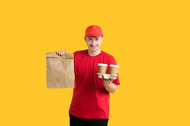 Mężczyzna kurier w czerwonej czapce i koszulce wydaje zamówienie fast foodów i napojów, na żółto