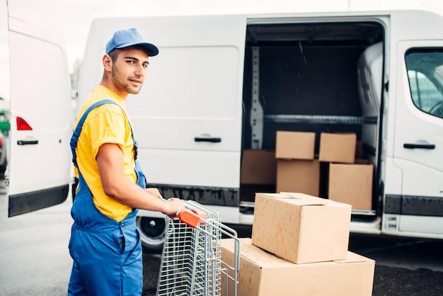 Mężczyzna kurier w mundurze pracy z ładunkiem, widok z tyłu