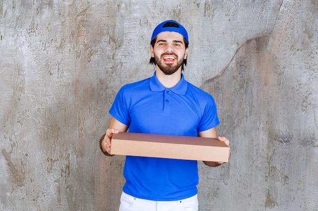 Mężczyzna kurier w niebieskim mundurze niosący kartonowe pudełko na wynos.