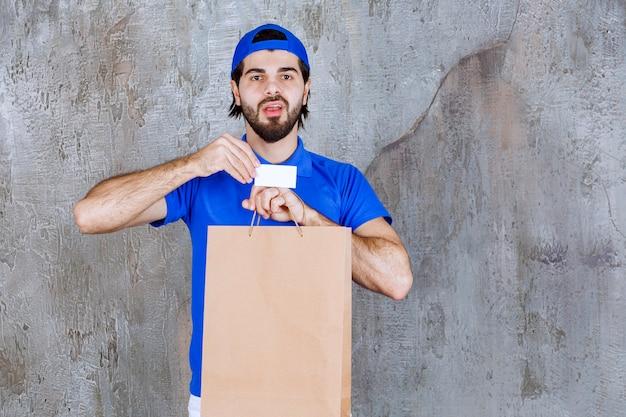 Mężczyzna kurier w niebieskim mundurze trzyma kartonową torbę na zakupy i prezentuje swoją wizytówkę.