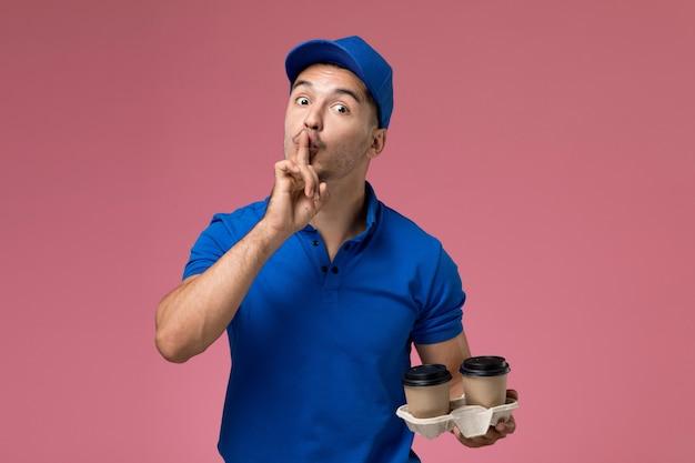 Mężczyzna kurier w niebieskim mundurze, trzymając brązowe filiżanki kawy pokazujące znak ciszy na różowym, jednolita dostawa usług pracownika