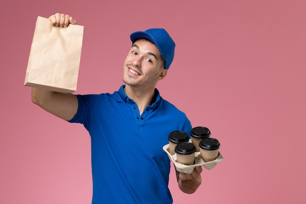 Mężczyzna kurier w niebieskim mundurze trzymając dostawę filiżanki kawy pakiet żywności na różowym, jednolitym dostawie usług pracy