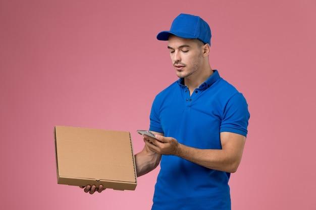 Mężczyzna kurier w niebieskim mundurze, trzymając pudełko żywności dostawy za pomocą swojego telefonu na różowym, jednolitym dostawie usług pracownika