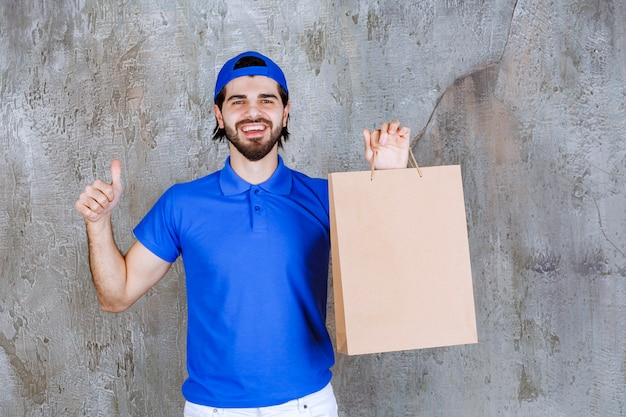 Mężczyzna kurier w niebieskim mundurze trzymający kartonową torbę na zakupy i pokazujący pozytywny znak ręki