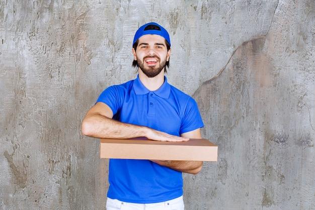 Mężczyzna kurier w niebieskim mundurze z kartonowym pudełkiem na wynos