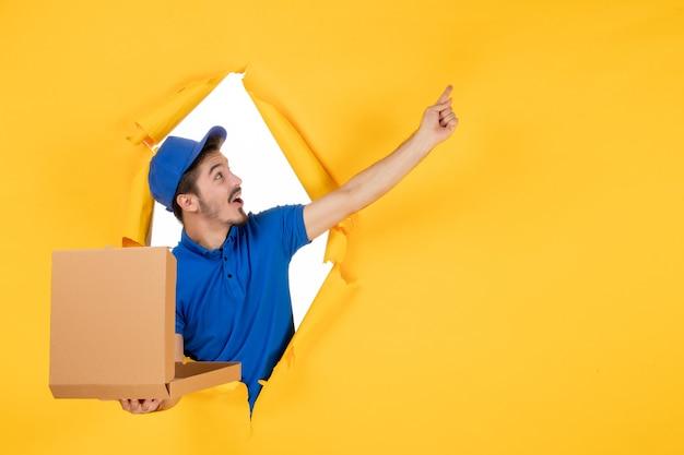 Mężczyzna kurier z widokiem z przodu trzymający otwarte pudełko po pizzy na żółtej przestrzeni