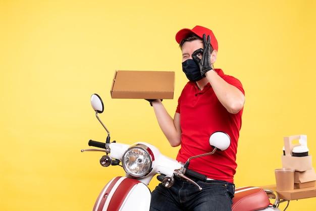 Mężczyzna kurier z widokiem z przodu w masce trzymającej pudełko na żywność na żółto