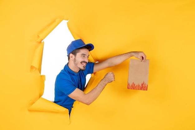 Mężczyzna kurier z widokiem z przodu w niebieskim mundurze, dający opakowanie żywności na żółtej przestrzeni
