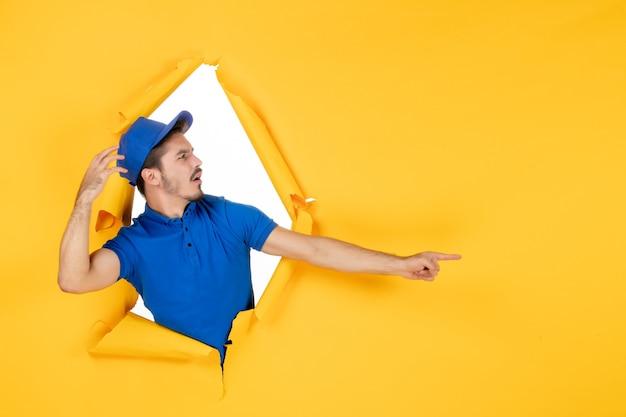 Mężczyzna kurier z widokiem z przodu w niebieskim mundurze na żółtej przestrzeni