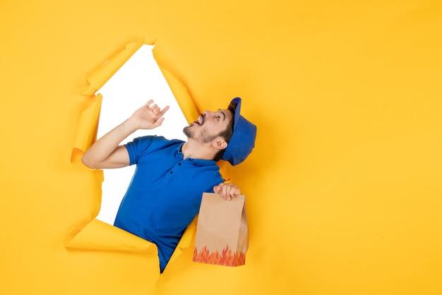 Mężczyzna kurier z widokiem z przodu w niebieskim mundurze trzymającym opakowanie żywności na żółtej przestrzeni