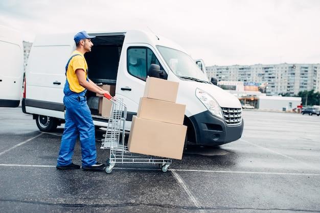 Mężczyzna kurier z wózkiem do paczek przed ciężarówką z kartonami. dystrybucja. dostawa ładunków. puste, przezroczyste pojemniki. usługi logistyczne i pocztowe