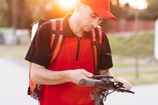 Mężczyzna kurierska dostawa jedzenia z czerwonym plecakiem termicznym idzie ulicą ze skuterem elektrycznym
