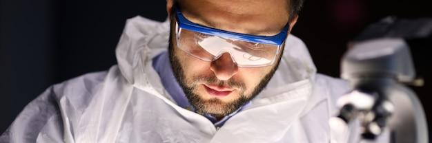 Mężczyzna laboratorium naprawia instrument blisko mikroskopu. rewolucyjna konstrukcja optymalizująca wydajność i zużycie energii. procesor instalacji lub wymiany, zasilacz. diagnostyka komputerowa