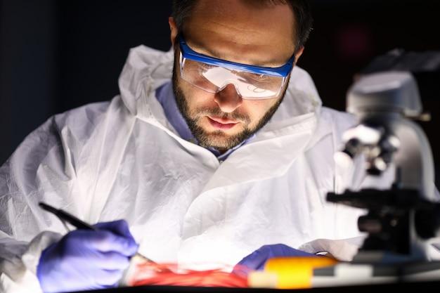 Mężczyzna laboratorium naprawia instrument blisko mikroskopu