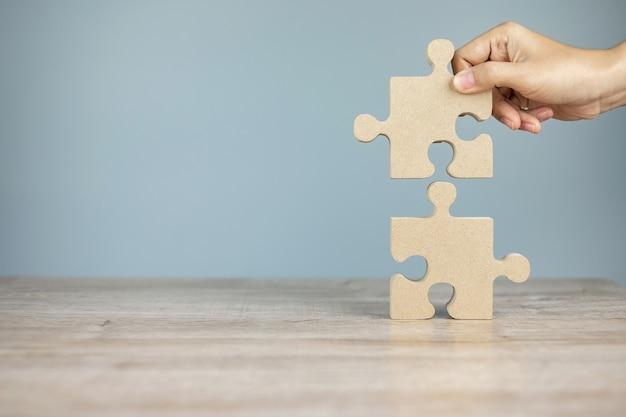 Mężczyzna łączy pary łamigłówki kawałek, drewniana wyrzynarka na stole. rozwiązania biznesowe, misja, sukces, cele i strategie