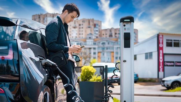 Mężczyzna ładujący swój samochód elektryczny na stacji ładującej i używający smartfona