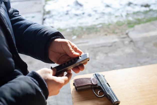 Mężczyzna ładuje broń kulami na ulicy