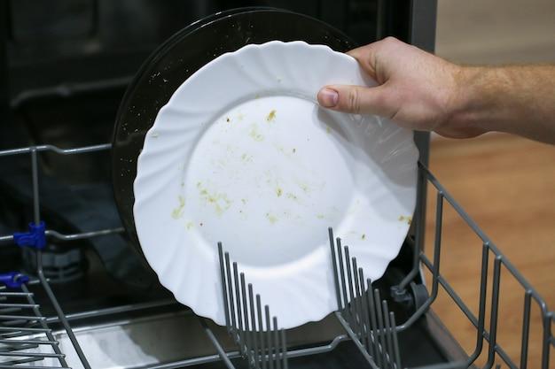 Mężczyzna ładuje brudne naczynia, talerze, łyżki, widelce, sztućce do tacy zmywarki.