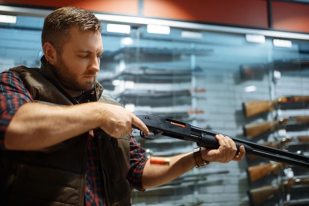 Mężczyzna ładuje nowy karabin przy kasie w sklepie z bronią
