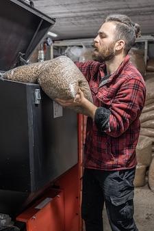 Mężczyzna ładuje pelety do kotła na paliwo stałe, pracuje z biopaliwami, oszczędne ogrzewanie.