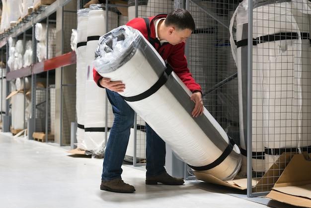 Mężczyzna ładuje rolkę materac w magazynie
