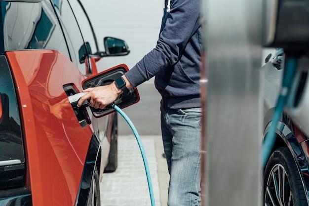 Mężczyzna ładuje samochód elektryczny na stacji ładującej