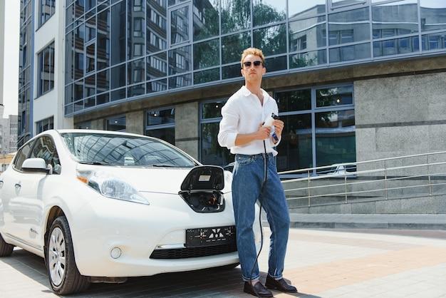 Mężczyzna ładuje swój luksusowy samochód elektryczny na stacji zewnętrznej przed nowoczesnymi nowymi budynkami miasta