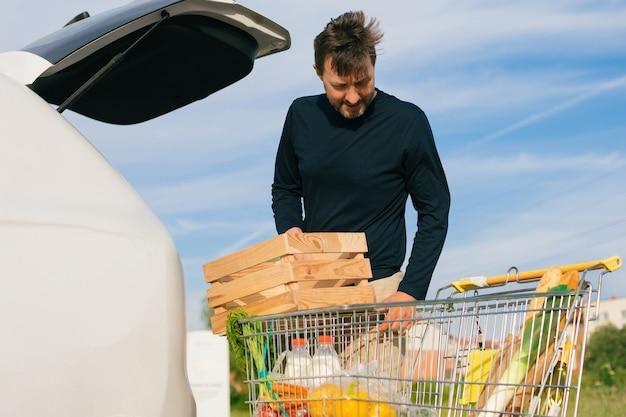 Mężczyzna ładuje zakupy do bagażnika. zamiast plastikowych toreb używa drewnianego pudełka. brak koncepcji plastiku